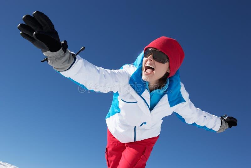 Kvinnan som har gyckel skidar på, ferie i berg royaltyfri foto