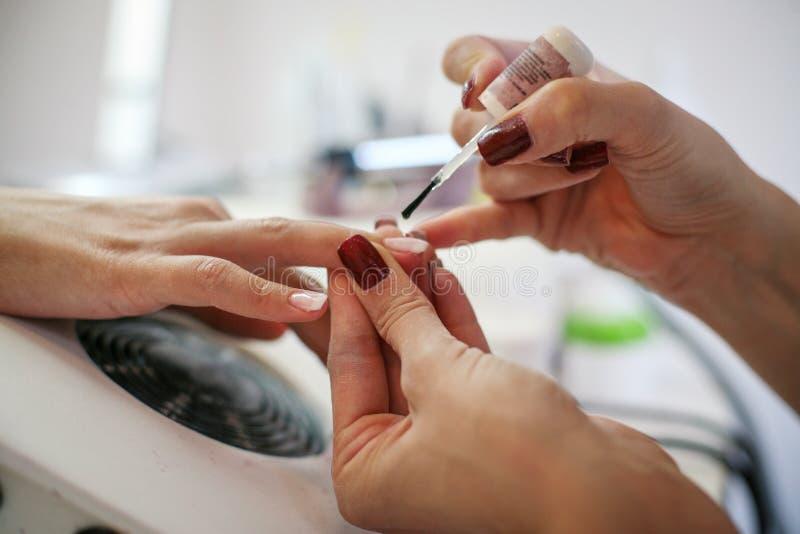 Kvinnan som har henne, spikar polerat på en skönhetsalong arkivbilder