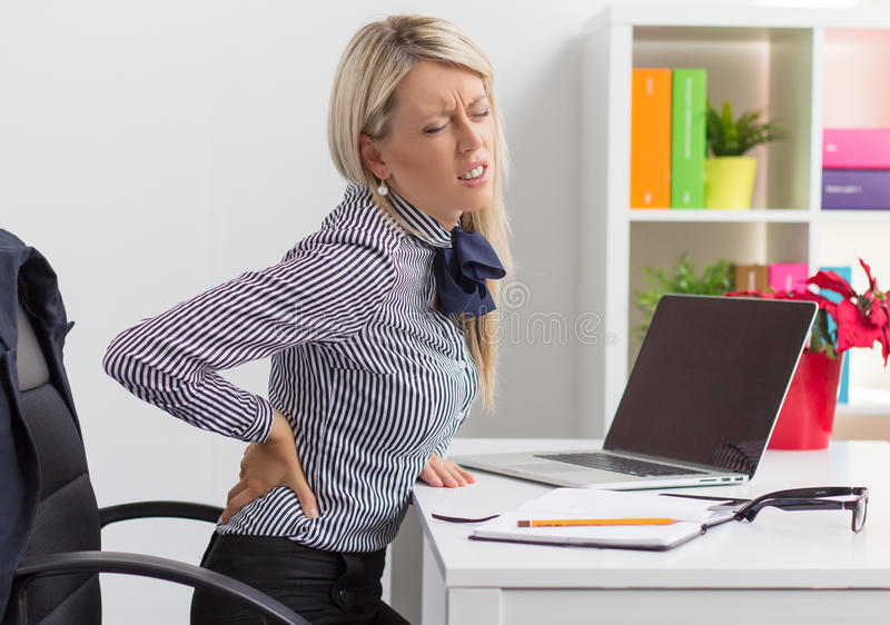Kvinnan som har tillbaka, smärtar, medan sitta på skrivbordet i regeringsställning arkivfoto