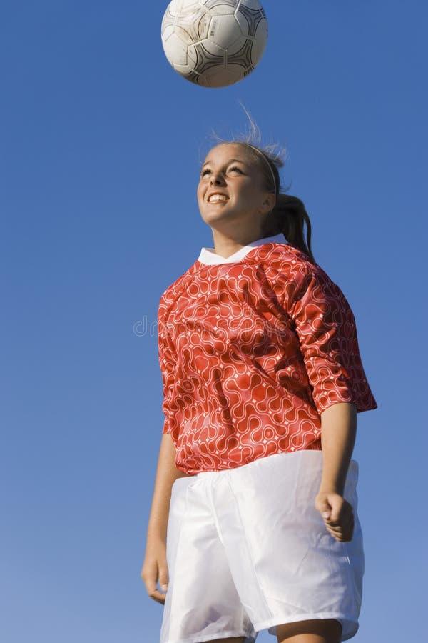 Kvinnan som Heading fotbollen, klumpa ihop sig royaltyfria foton