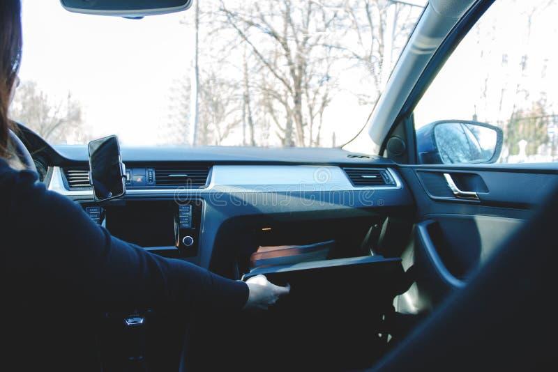 Kvinnan som kör, öppnar handskeasken till lagerdokument royaltyfri bild