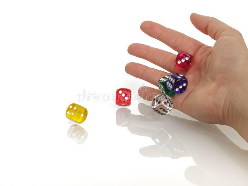 Kvinnan som kastar något färgrikt, tärnar med hennes händer som isoleras på vit bakgrund Spela, kasino och affärsidé royaltyfri foto