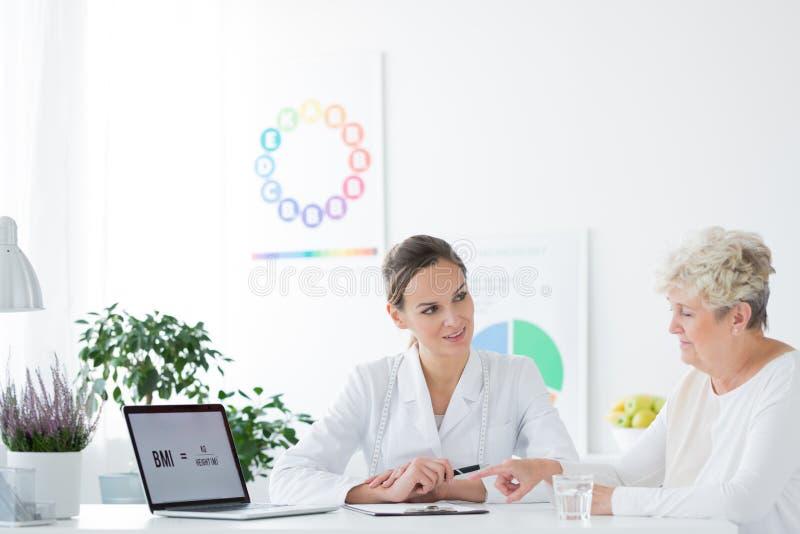 Kvinnan som konsulterar, bantar med dietitianen arkivbild