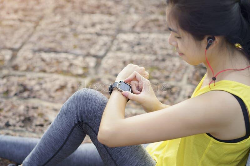 Kvinnan som kontrollerar framsteg på den smarta klockan för att förbinda, lyssnar musik till hörluren, wearable konditionapparat  arkivbilder