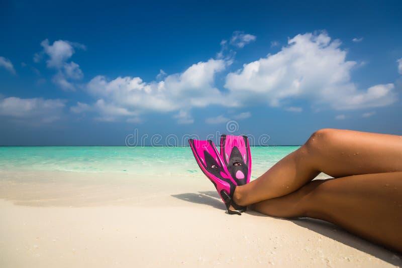 Kvinnan som kopplar av på sommarstrandsemester, semestrar att ligga i sand royaltyfri fotografi