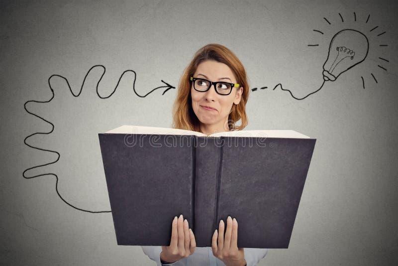 Kvinnan som läser en enorm bok, har en bra idé royaltyfri bild