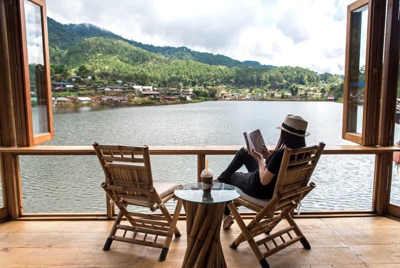 Kvinnan som läser kaffe för bokligga och drinkis på stolen i den wood terrassen mot härlig sikt, kopplar av och den lyckliga dage arkivfoto