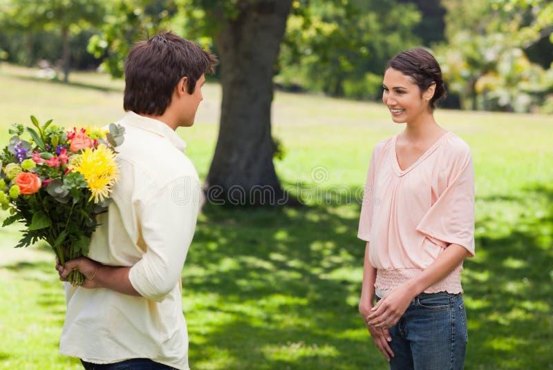 Kvinnan som ler som henne vännen, att närma sig henne med blommor fotografering för bildbyråer
