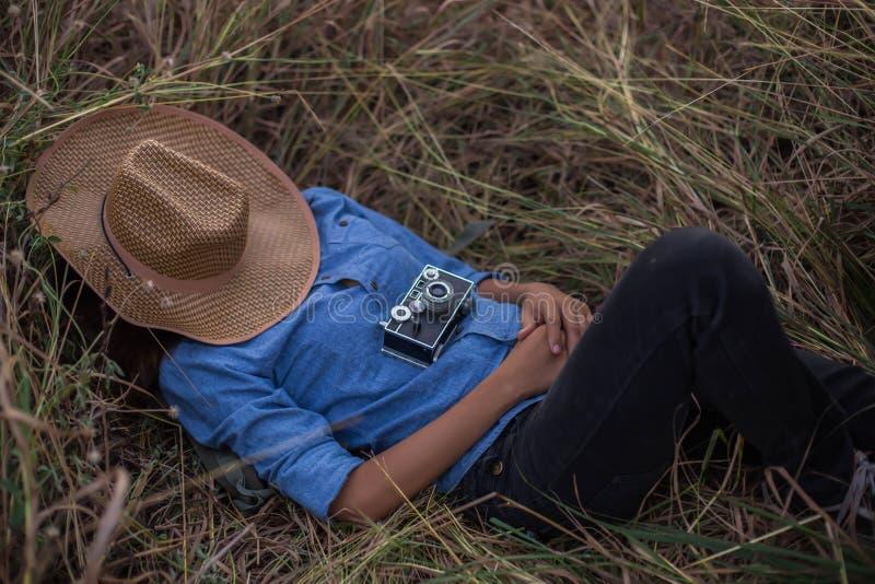 Kvinnan som ligger i, parkerar med en kamera och en hatt royaltyfria foton