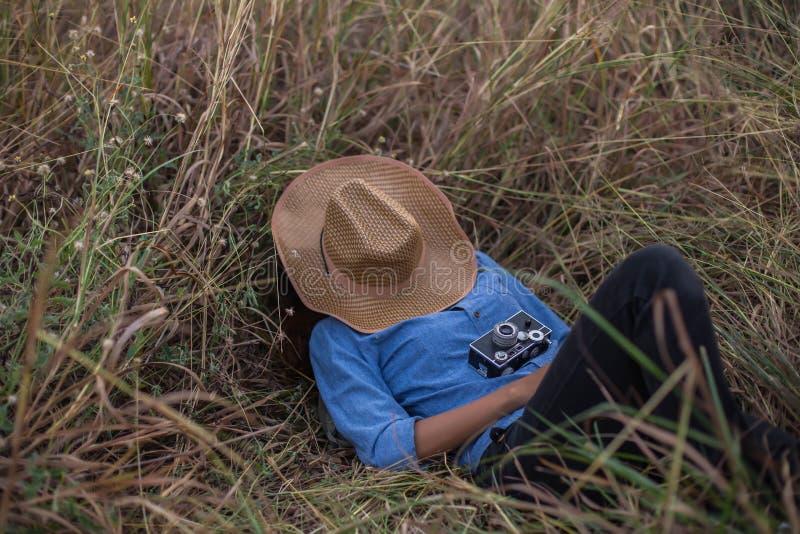 Kvinnan som ligger i, parkerar med en kamera och en hatt royaltyfria bilder