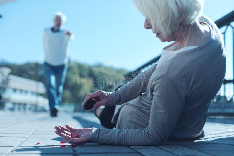 Kvinnan som ligger på trottoaren som tar preventivpillerar till lättnad, smärtar arkivfoto