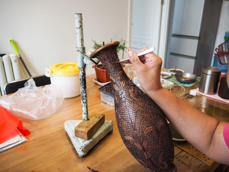 Kvinnan som limmar den mycket lilla formade cloisonnen, binder till en kopparvascreati fotografering för bildbyråer
