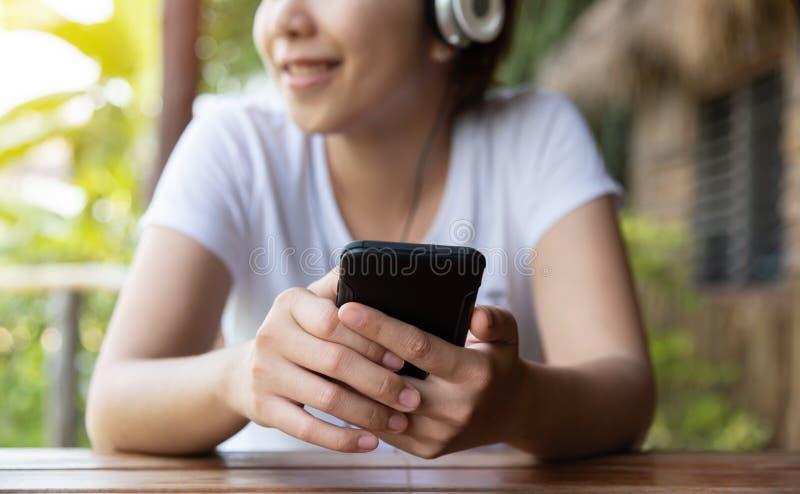 Kvinnan som lyssnar till musiken med headphonen och, ilar telefonen arkivfoton