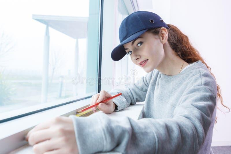 Kvinnan som mäter fönstret, förser med rutor royaltyfria bilder