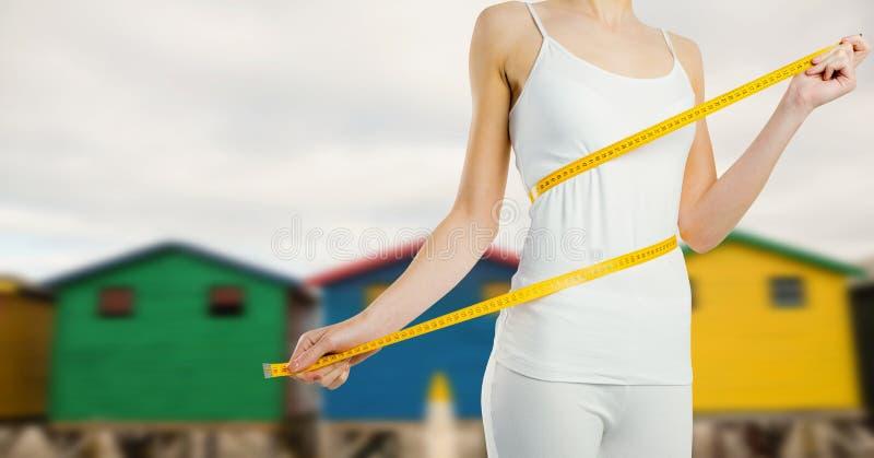 Kvinnan som mäter vikt med att mäta bandet på midjan nära sommarstranden, förlägga i barack arkivfoton