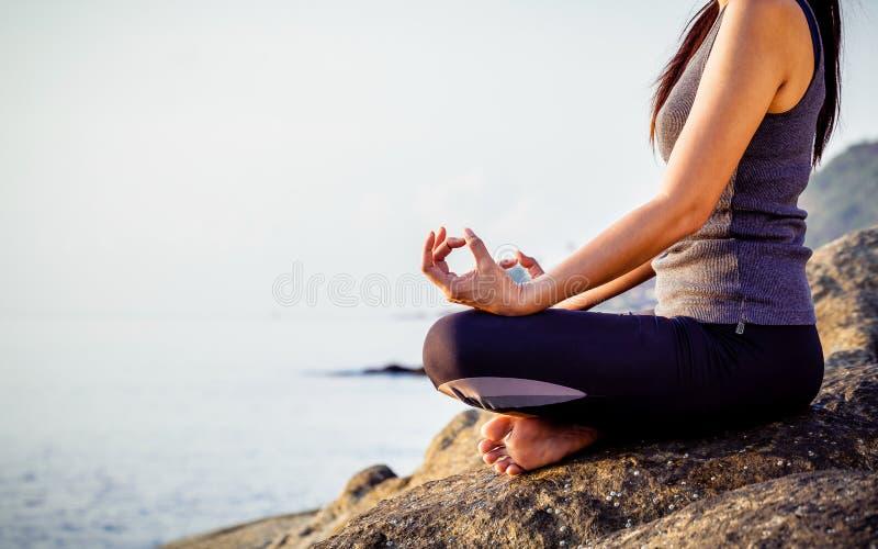 Kvinnan som mediterar i en yoga, poserar på den tropiska stranden Femal royaltyfria bilder