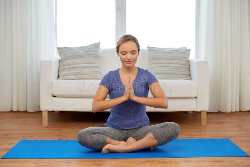 Kvinnan som mediterar i lotusblomma, poserar hemma arkivfoto