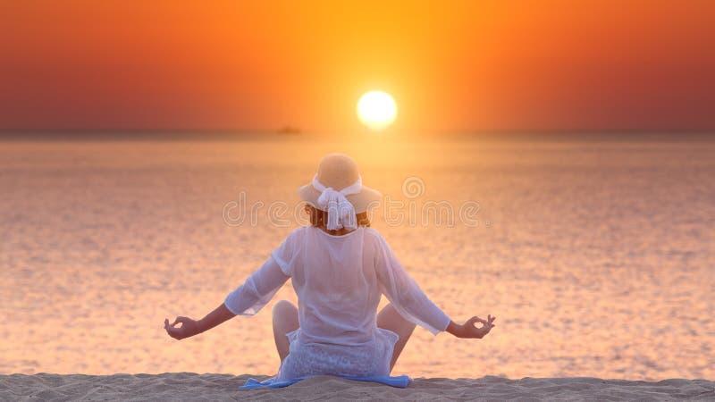 Kvinnan som mediterar i yoga, poserar på stranden på den härliga solnedgången royaltyfri bild