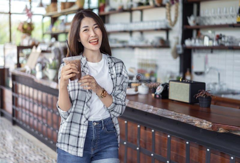 Kvinnan som rymmer exponeringsglas av med is choklad, mjölkar i ett kafé royaltyfria bilder