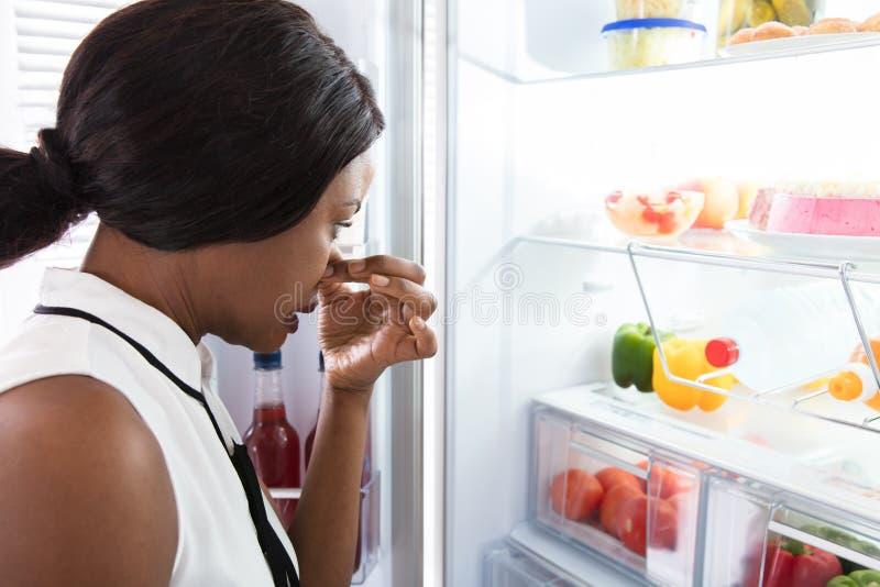 Kvinnan som rymmer hennes näsa nära, trasslar till mat i kylskåp royaltyfri fotografi