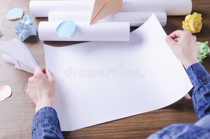 Kvinnan som rymmer tom affärsplanläggning, skissar Begrepp av processen av idékläckning och att tänka om ny idé T?m utrymme f?r d royaltyfria bilder