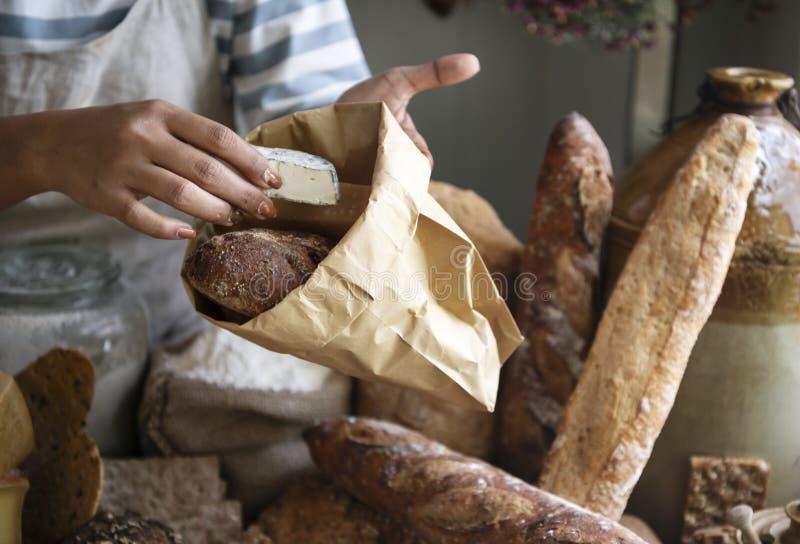 Kvinnan som säljer ost till en kund på en lantgård, shoppar royaltyfri fotografi