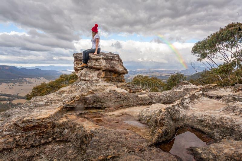Kvinnan som sätta sig på, vaggar pelarmaximumet med de bästa sikterna nedanför att trotsa bergkylan royaltyfri bild