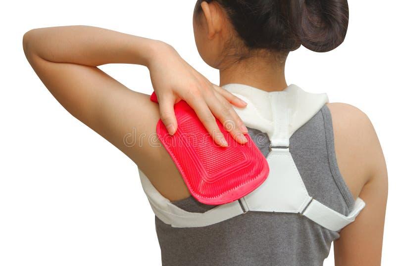Kvinnan som sätter en varm packe på hennes skuldra, smärtar royaltyfri foto