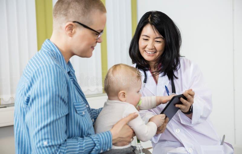 Kvinnan som ser, behandla som ett barn den gripande Digital minnestavlan från kvinnlig doktor royaltyfria foton