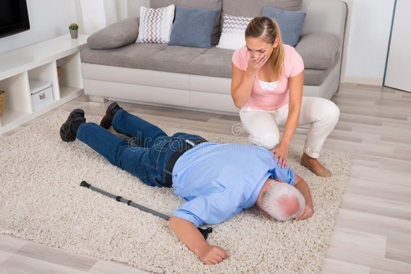 Kvinnan som ser henne, svimmade den rörelsehindrade fadern royaltyfri bild
