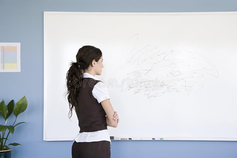 Kvinnan som ser, klottrar på whiteboard royaltyfri bild