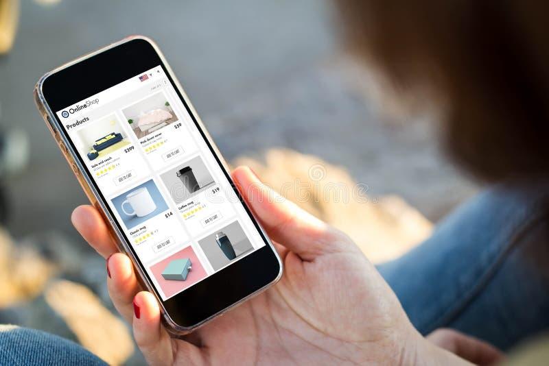 kvinnan som sitter i gatan som rymmer hennes smartphonevisning shoppar direktanslutet royaltyfri fotografi