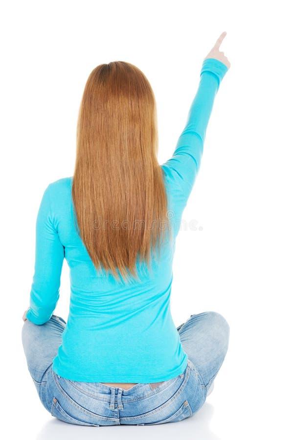 Kvinnan som sitter och pekar upp, beskådar tillbaka. royaltyfria bilder