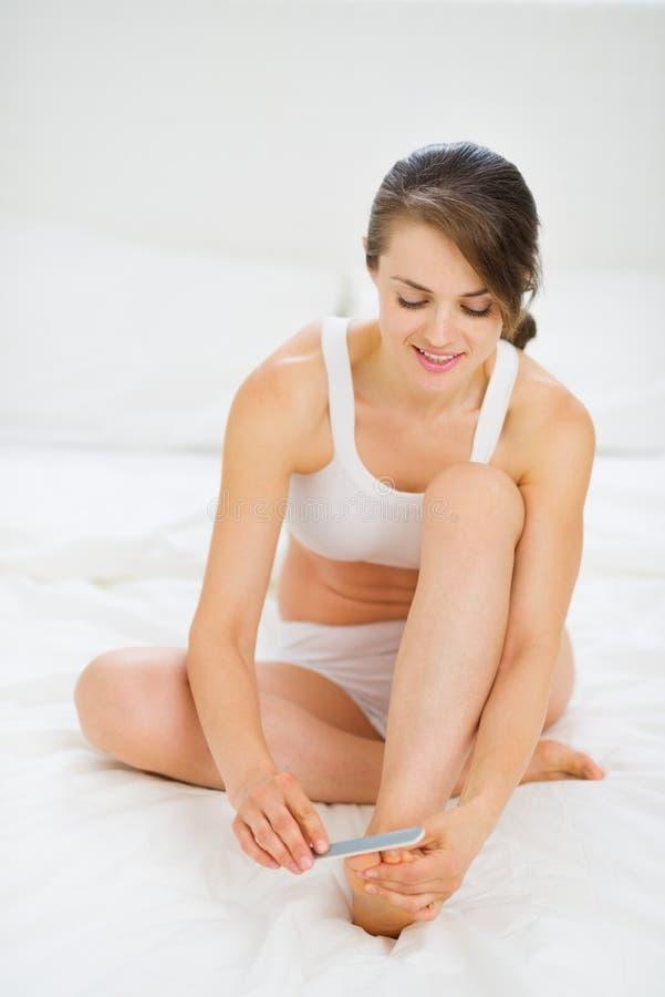 Kvinnan som sitter på underlag och tar omsorg av, spikar royaltyfri foto