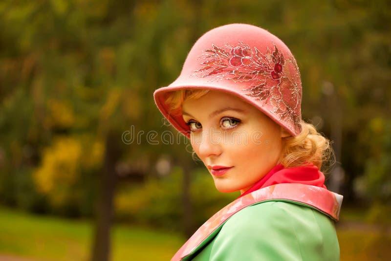 Kvinnan som slitage den retro filthatten, och ull coat royaltyfria bilder