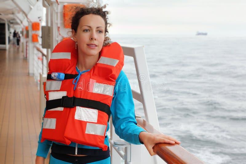 Kvinnan som slitage i flytväst, ser in i avstånd arkivbilder