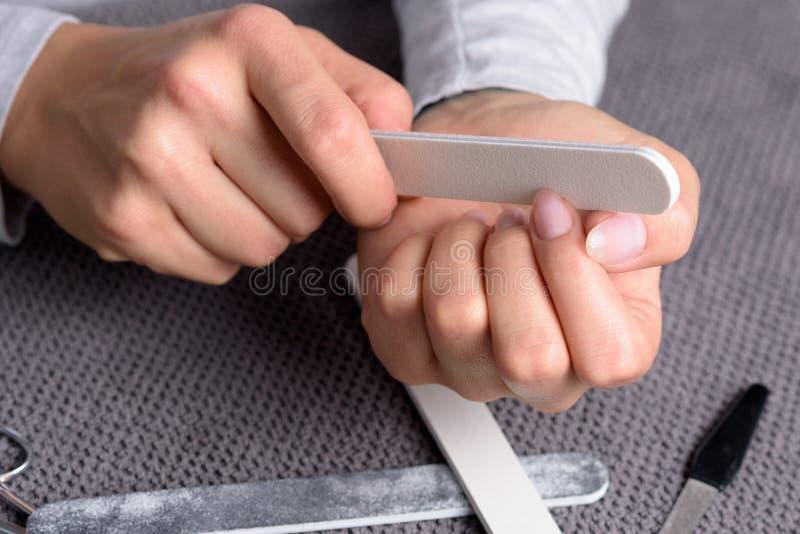 Kvinnan som sparar hennes finger, spikar royaltyfria bilder