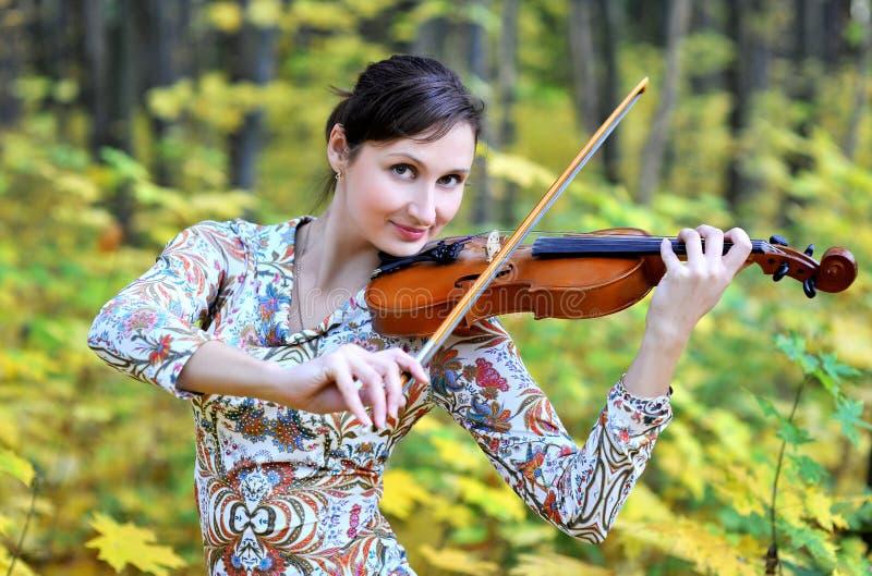 Kvinnan som spelar fiolen i hösten, parkerar royaltyfri bild