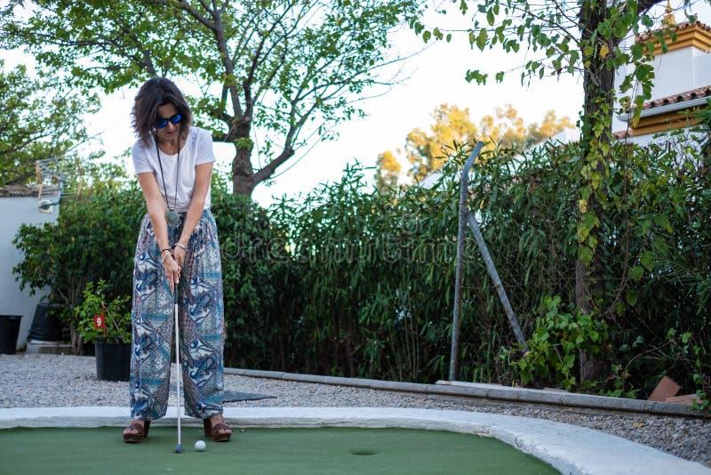 Kvinnan som spelar minigolf, ordnar till för att slå bollen med en pinne royaltyfri bild