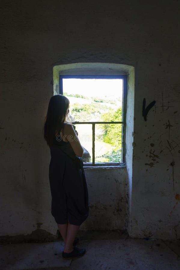 Kvinnan som står det främsta fönsterhålet av ett gammalt, brocken och kasserade huset royaltyfri foto