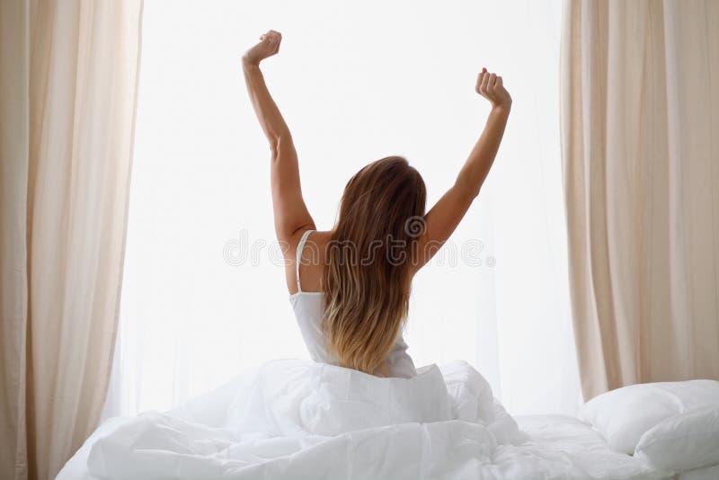 Kvinnan som sträcker i säng efter vak upp, beskådar tillbaka och att skriva in en avkopplad dag som är lycklig och efter sömn för fotografering för bildbyråer