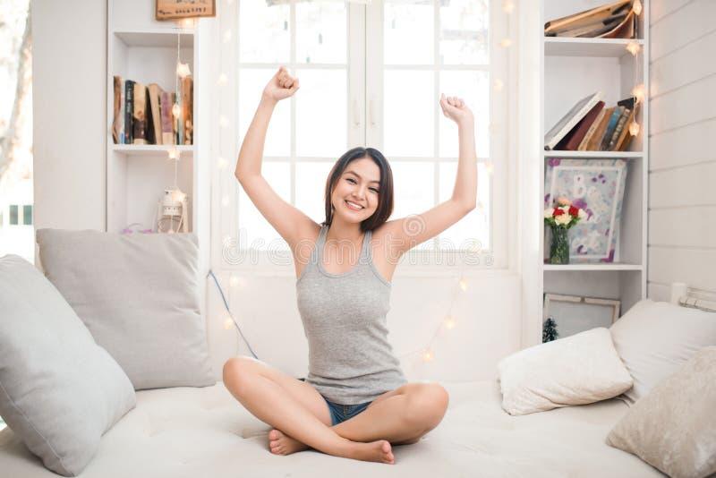 Kvinnan som sträcker i säng, når han har vaknat upp, beskådar tillbaka och att skriva in en avkopplad dag som är lycklig och efte royaltyfria bilder
