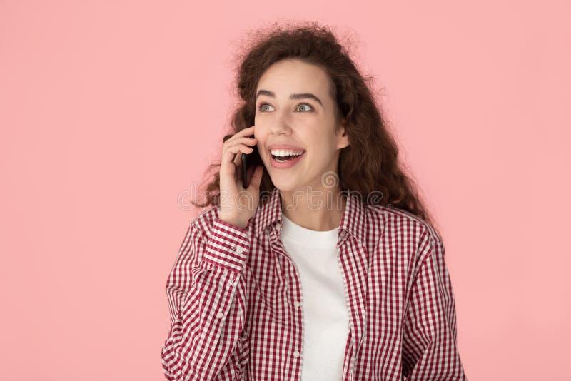 Kvinnan som talar på mobiltelefonen, känner det spännande studioskottet royaltyfri fotografi