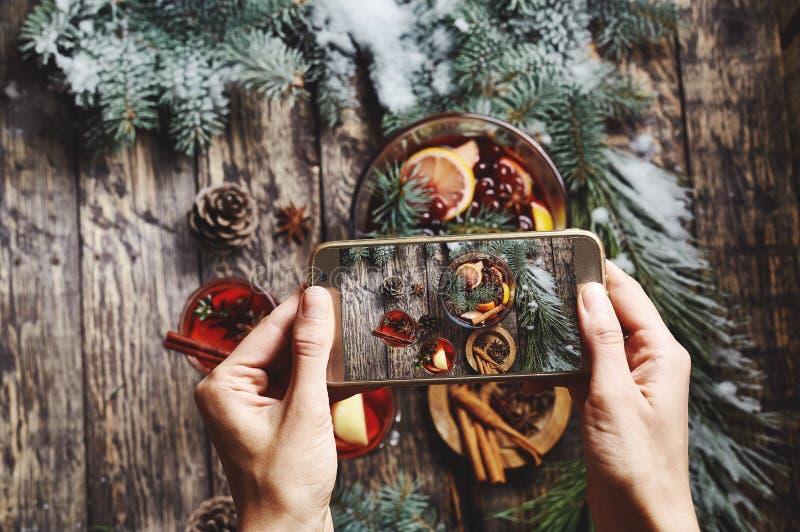 Kvinnan som tar bilder av exponeringsglasbunken med jul, funderade vin på träbakgrund arkivbild