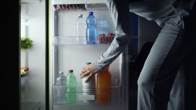 Kvinnan som tar en flaska av, mj?lkar fr?n kylen arkivbild