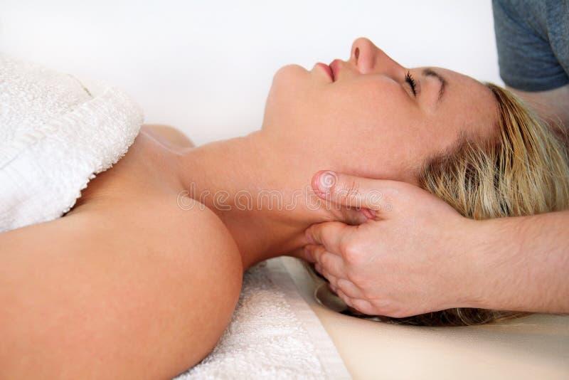 Kvinnan som tar en massagehals, tränga sig in på massagetabellen royaltyfri fotografi