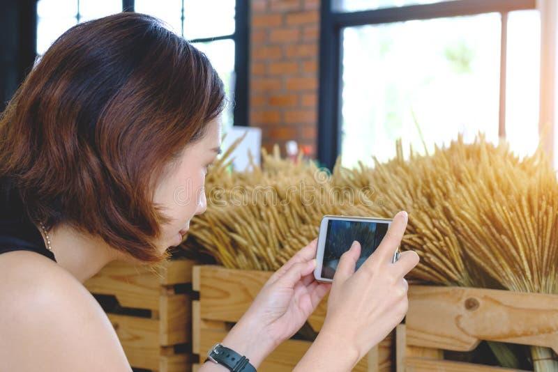Kvinnan som tar fotoet med mobiltelefonen, den unga thai flickan, tar fotoet royaltyfri fotografi