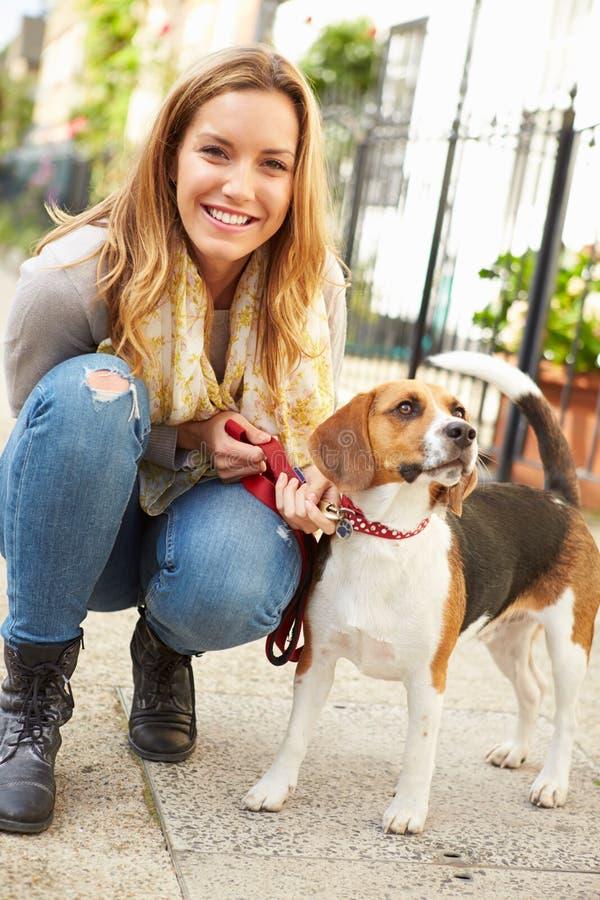 Kvinnan som tar hunden för, går på stadsgatan royaltyfri foto