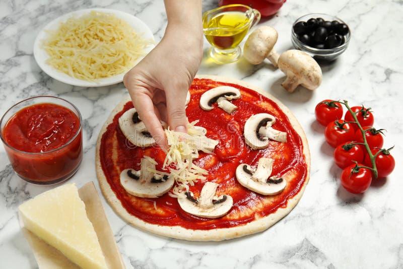 Kvinnan som tillfogar grated ost till unbaked pizza på, marmorerar tabellen arkivbilder