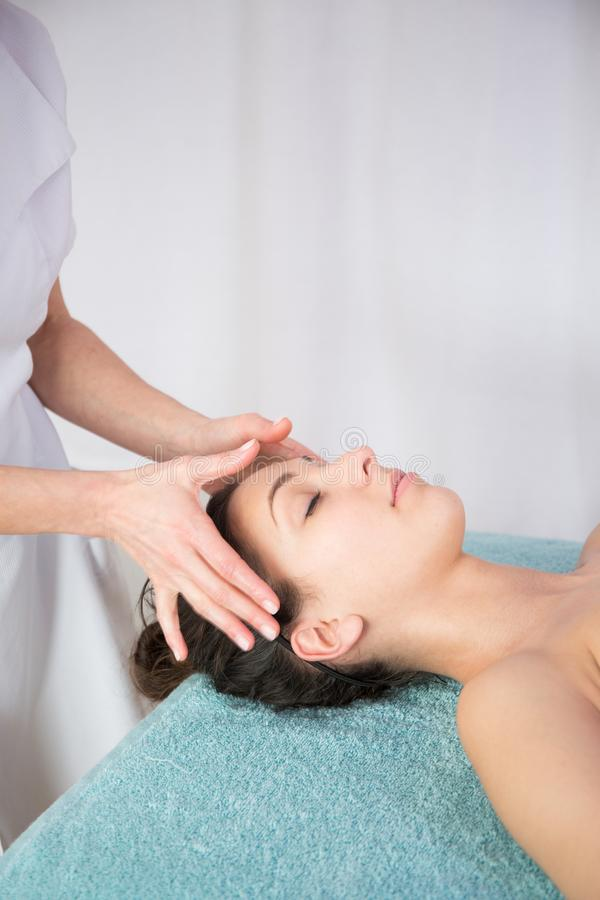 Kvinnan som tycker om anti-åldras ansikts- massage en nätt flicka, får yrkesmässig hudomsorg i wellnessmitt Avkoppling skönhetbru royaltyfri foto